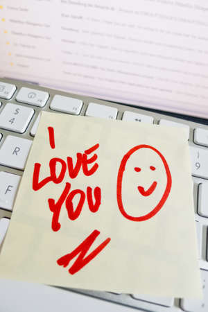 dear: a sticky note on the keyboard of a computer is to remember  i love you Stock Photo