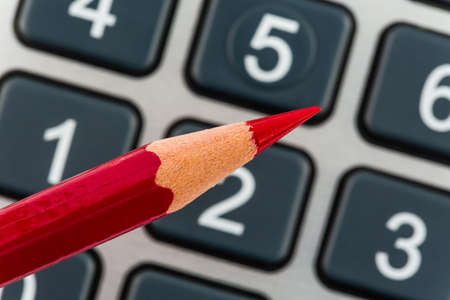cutback: a red pen is on a calculator  save on costs, expenses and budget for bad economy Stock Photo