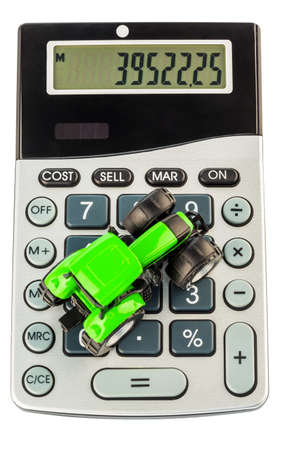 ongoing: a tractor is on a calculator  costs for fuel, insurance and wear  costs and subsidies in agriculture