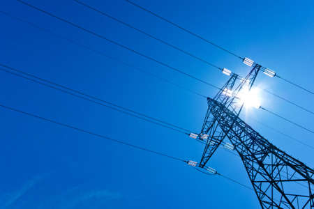 the mast of a high voltage power line with sun and blue sky  energy supply by power line  photo