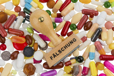 counterfeiting: stamp on colorful tablets, symbolic photo for drug counterfeiting and piracy Stock Photo