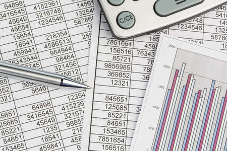 profitability: a calculator is on a balance sheet numbers are statistics  photo icon for sales, profits and costs