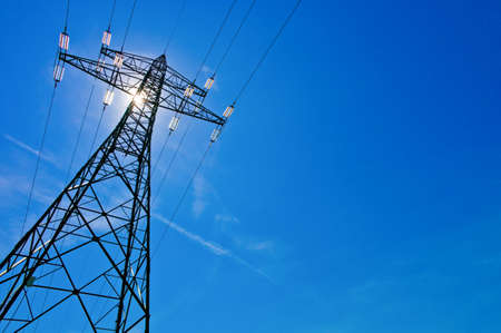 a high voltage power pylons against blue sky and sun rays photo