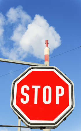 chimney of an industrial company and stop sign  symbolic photo for environmental protection and ozone  photo