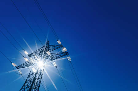 electricity grid: a high voltage power pylons against blue sky and sun rays