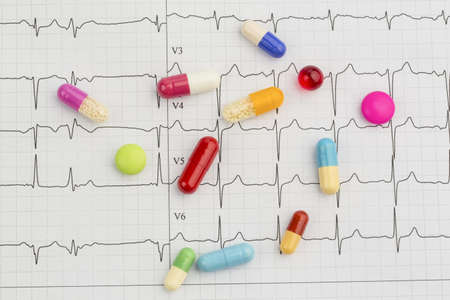 several tablets are on an ekg  symbolic photo for diseases of the heart and circulation photo