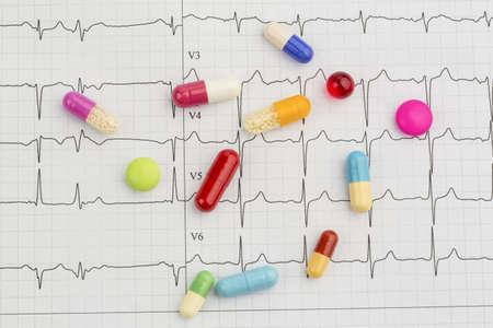 angina: varias tabletas están en una foto simbólica ekg para las enfermedades del corazón y la circulación