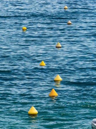 floater: yellow buoys floating in the sea as a boundary Stock Photo