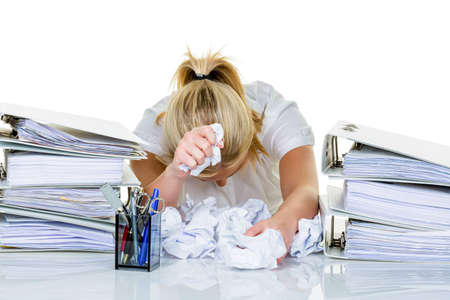 postpone: young woman in office is overwhelmed with work  burnout in work or study  Stock Photo