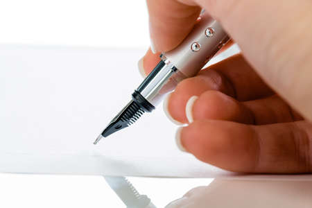 notieren: a hand with a pen Stock Photo