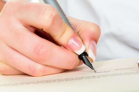 testament schreiben: eine Frau unterschreibt einen Vertrag oder ein Testament mit einem Stift