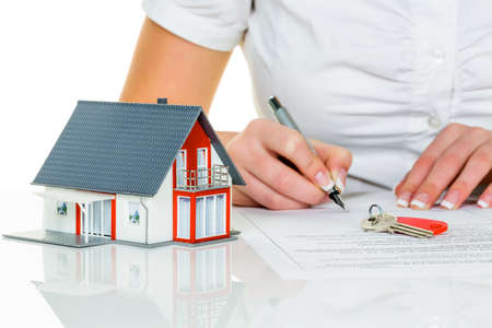 plot: a woman signs a purchase contract for a home with a real estate agent  Stock Photo