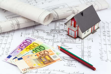 construction draftsman: banknotes of euros currency lying on a house plan Stock Photo