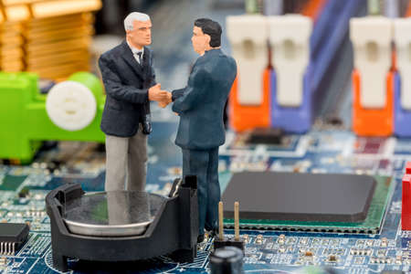 digitization: two managers talk on the motherboard of a computer standing
