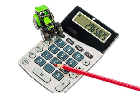 a tractor and a red pen is on a calculator Stock Photo - 20772760