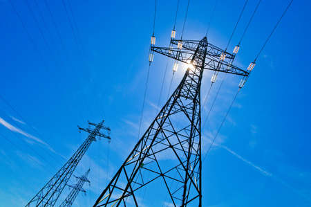 power cable: a power mast of a high voltage transmission line against blue sky with sun