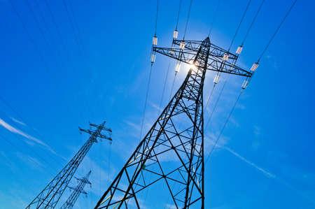 un mástil de potencia de una línea de transmisión de alta tensión contra el cielo azul con el sol Foto de archivo