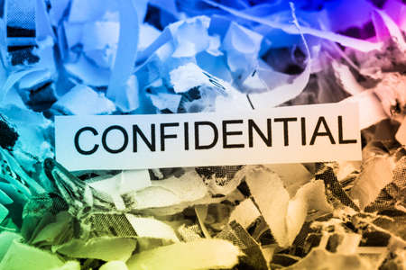 paper shredder: scraps of paper with the word confidential Stock Photo