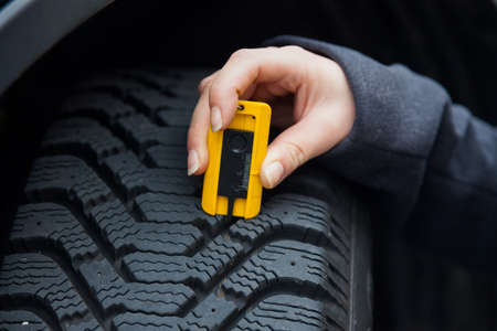 tyre tread: a young woman is measuring the tread depth of her car tire