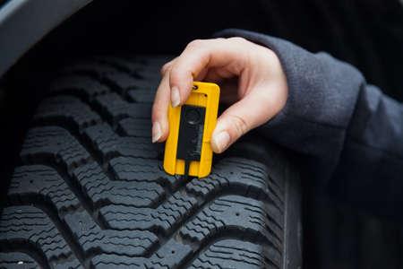 una giovane donna sta misurando la profondità del battistrada dei pneumatici della sua auto