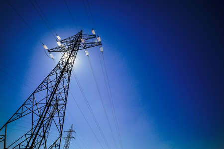transmission line: a power mast of a high voltage transmission line against blue sky with sun