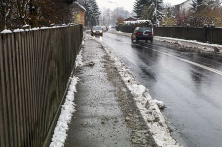 eviction: snow on sidewalk and street, symbol for accident risk and photo räumpflicht Stock Photo
