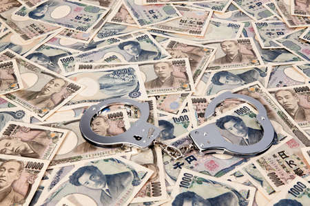 seem: yen banknotes, currency from japan with handcuffs  crime in the economy Stock Photo