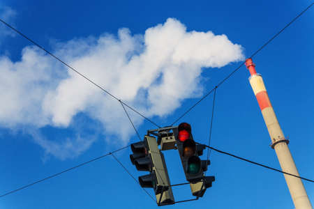 chimney of an industrial company and a red traffic light. symbolic photo for environmental protection and ozone. photo