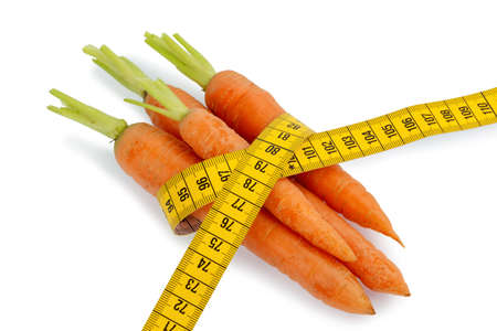 thinness: organically grown carrots with tape. fresh fruit and vegetables are always healthy. photo icon for healthy diet.