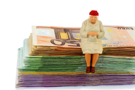 incapacitated: figure of an old woman sitting on a stack of bills, symbolic photo for pension and retirement