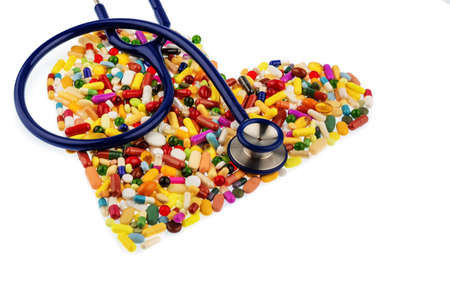 therapie: stethoscope and pills in heart-shaped arrangement, symbol photo for heart disease, diagnosis and medication