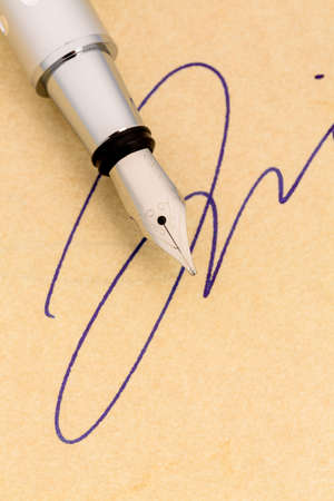 notieren: a fountain pen and a signature on yellow paper. symbolic photo for contract, and graphology testament Stock Photo