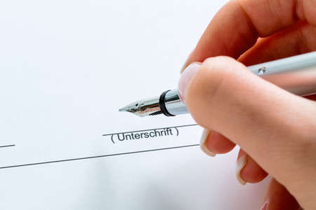 a hand with a fountain pen in the untrerschrift under a contract or testament. photo