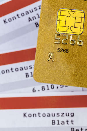 overdraft: a gold credit card and bank statement .. symbolic photo for cashless transactions and status symbols.