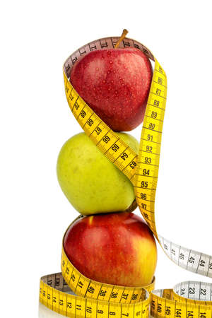 free weight: several apples with a tape measure. symbolic photo for diet and healthy, vitamin-rich diet. Stock Photo
