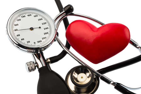 presure: a blood pressure meter, a heart and stethoscope lying on a white background