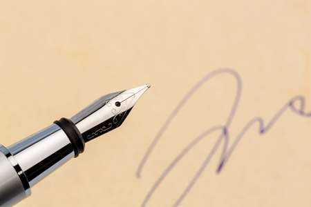 legacy: a fountain pen and a signature on yellow paper. symbolic photo for contract, and graphology testament Stock Photo