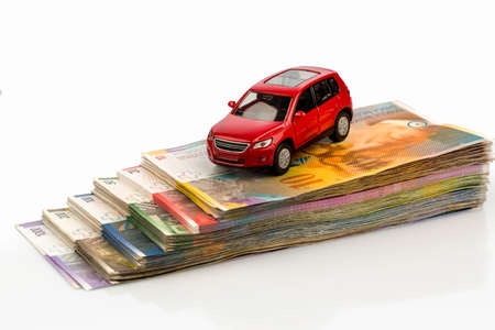 refuel: a car is parked in swiss francs banknotes. cost of buying a car, gasoline, car insurance and other costs
