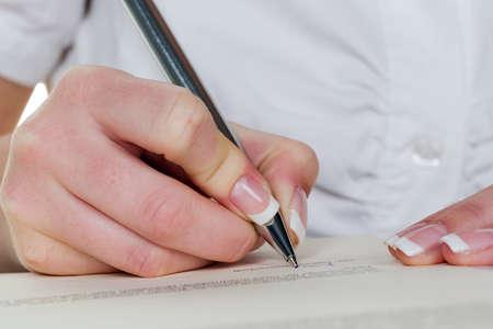 eine Frau unterschreibt einen Vertrag oder ein Testament mit einem F�llfederhalter. Lizenzfreie Bilder