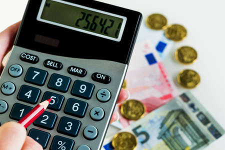 hand with calculator and bills. symbolic photo for revenue, profit, taxes and costing