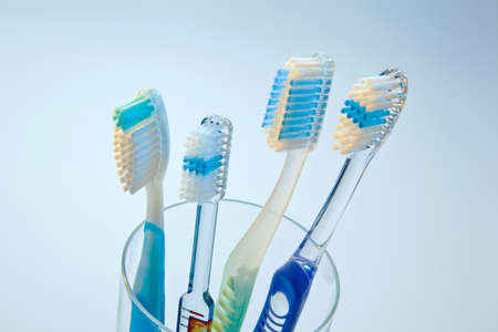 several toothbrushes in a cup waiting for the teeth cleaning.