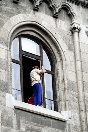 putz: a woman cleans windows and stands dangerously on the window ledge