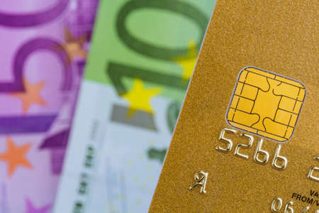 cashless: a gold credit card and euro banknotes. symbolic photo for cashless transactions and status symbols.