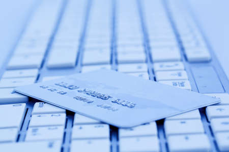 indebtedness: close-up a credit card for cashless payment and keyboard. photo icon for shopping on the internet. Stock Photo
