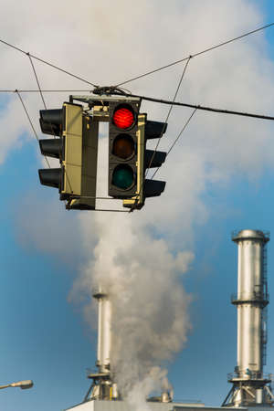 ozone: chimney of an industrial company and a red light. symbolic photo for environmental protection and ozone.