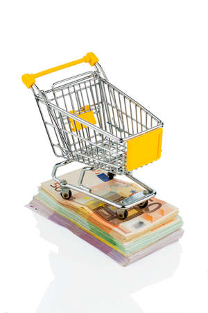 consumerist: shopping cart is on banknotes, symbolic photo for shopping, purchasing power, money printing and inflation