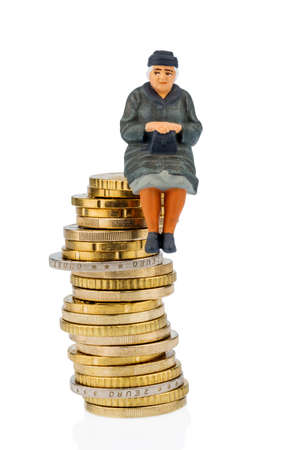 oldage: pensioner sitting on a pile of money, symbolic photo for pensions, retirement, old-age security