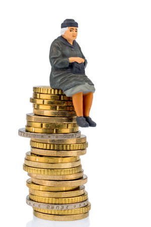 pensioner sitting on a pile of money, symbolic photo for pensions, retirement, old-age security photo