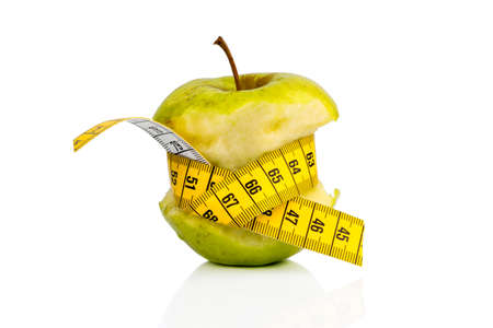 apple with a measuring tape. symbolic photo for diet and healthy, vitamin-rich diet. Stock Photo