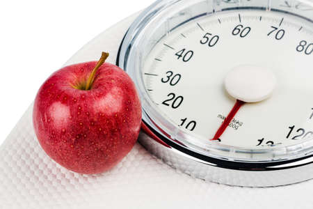 on a personal scale is an apple. symbolic photo for weight loss and healthy, vitamin-rich diet. photo
